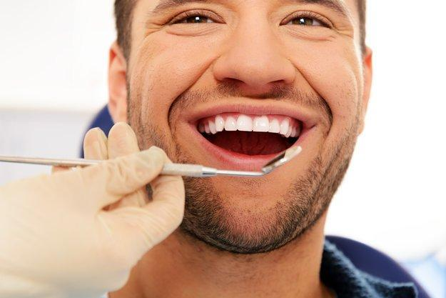 man smiling with dental mirror in front of mouth