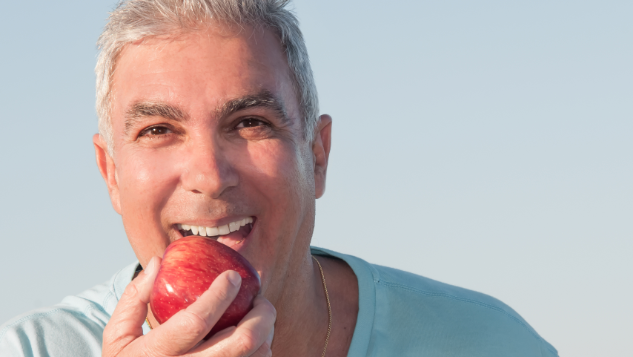 Older man eating apple